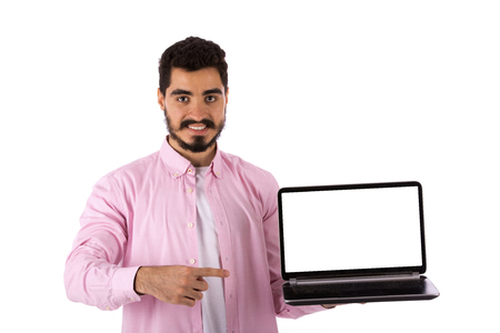 Handsome happy beard young man smiling and pointing to a laptop, guy wearing pink shirt, isolated on white background Banco de Imagens