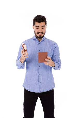 Handsome happy beard young man smiling and opening a brown gift box, guy wearing blue shirt, isolated on white background
