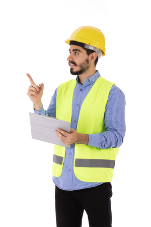 Happy beard engineer holding a clipboard and pointing to something, guy wearing blue shirt and yellow vest with a helmet, isolated on white background