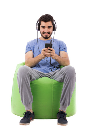 Handsome happy young man with headphones sitting on a green chair a and listening to music, guy holding a cellphone and wearing blue t-shirt, isolated on white background
