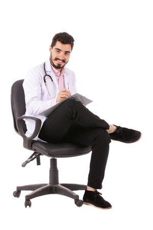 Happy beard young doctor in white lab coat with stethoscope sitting on a chair and taking some notes, isolated on white background Banco de Imagens