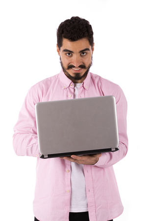 Handsome happy beard young man smiling and using a laptop, guy wearing pink shirt, isolated on white background Banco de Imagens