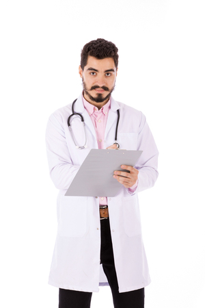 Happy beard young doctor in white lab coat with stethoscope smiling and taking some notes, isolated on white background Banco de Imagens