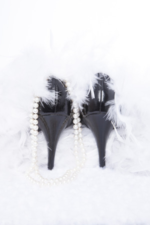 A pair of sexy, black leather pumps sit atop a white fur surface with a white background; pearls and a white boa surround the shoes photo