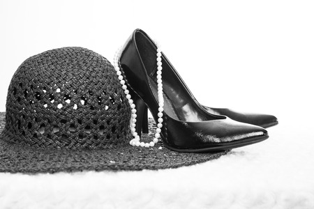 A pair of sexy, black leather pumps sit atop a white fur surface with a white background; pearls and a black hat surround the shoes photo
