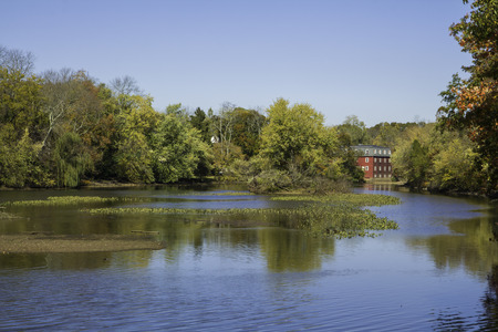 Fall foliage is reflected in the water at Delaware and Raritan Canal State Park in Princeton, New Jersey   An old red mill house can be seen in the background