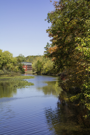 Fall foliage is reflected in the water at Delaware and Raritan Canal State Park in Princeton, New Jersey   An old red mill house can be seen in the background  photo