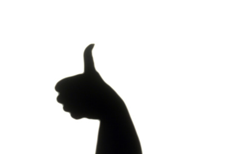 alright: An abstract shadow of a hand giving the thumbs up sign on pure white background