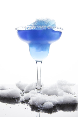 bartend: A margarita glass is filled with a blue frozen margarita; white sugar coats the rim; slushy snow sits around the base of the glass and is reflected off the surface; white background
