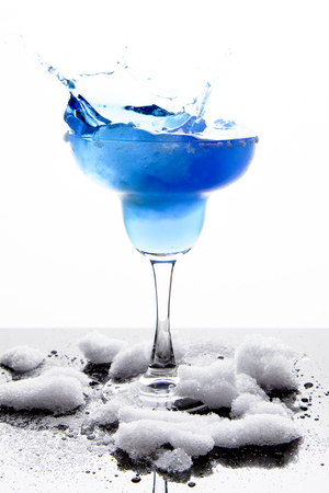 bartend: A margarita glass is filled with a blue frozen margarita; white sugar coats the rim; slushy snow sits around the base of the glass and is reflected off the surface; white background; the drink splashes out of the side of the glass Stock Photo