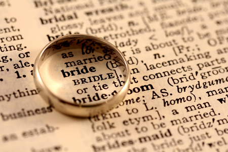 A wedding band sits atop the word bride in the dictionary, circling it photo