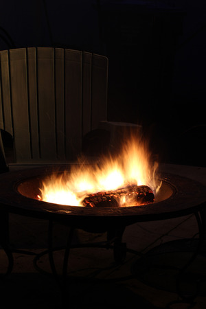 A campfire burns in the dark with an Adirondak chair behind it
