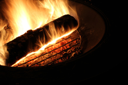 A burning log is atop a campfire pit; red hot embers burn below; timed exposure Stock Photo