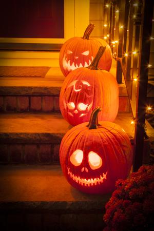 Drie jack-o-lantaarns zitten op een veranda voor Halloween met personages uit de Nightmare Before Christmas en de Monster High skelet