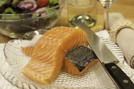 napkin ring: Two pieces of fresh salmon sit atop a plate ready to be cooked.  A sharp knife rests on the side of the plate.  In the background can be seen a fresh, colorful salad, a wine bottle and glass, and a napkin with napkin ring.