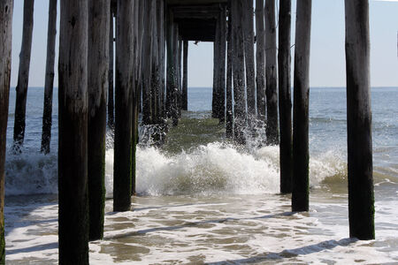 piling: Waves crash under the fishing pier in Ocean City, Maryland