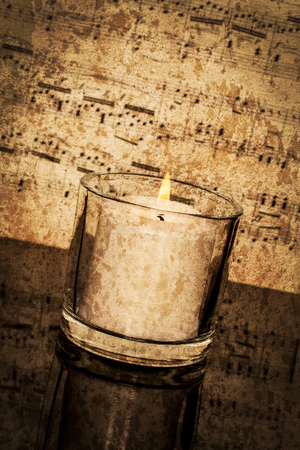 timeless: Old classical sheet music has a vintage tone and texture to it; vertical format; candle burning in foreground