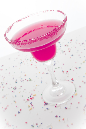 responsibly: A hot pink margarita in a margarita glass with pink sugar on the rim; festive sprinkles surround it Stock Photo