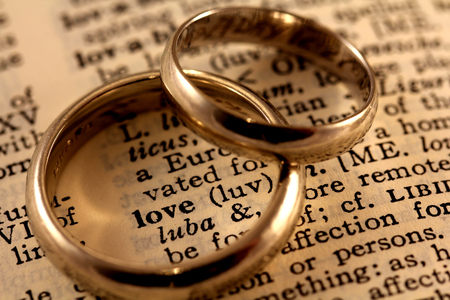 The word love in the dictionary with two wedding bands atop to circle the word