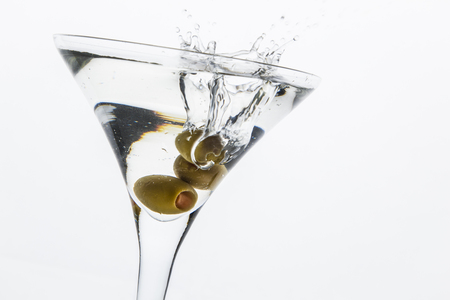 bartend: A martini glass on a white background; the water ripples and splashed as a green spanish olive with pimento is dropped into the glass; horizontal format