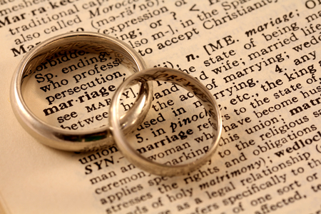 The word marriage in the dictionary with two wedding bands atop, circling the word
