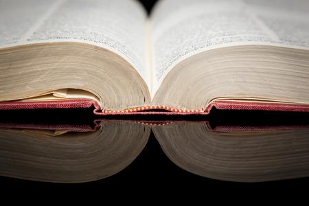 Ein altes Buch auf einer glänzenden schwarzen Oberfläche reflektiert Standard-Bild - 27935315