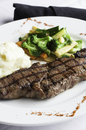 A white plate holds a delicious grilled New York Strip Steak with a side of mashed potatoes and fresh mixed vegetables   A napkin roll of utensils sits aside the plate