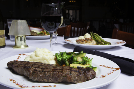 A white plate holds a delicious grilled New York Strip Steak with a side of mashed potatoes and fresh mixed vegetables   A glass of red wine completes the meal   Other dishes and drinks can be seen in the background   Everything is atop a white tablecloth photo