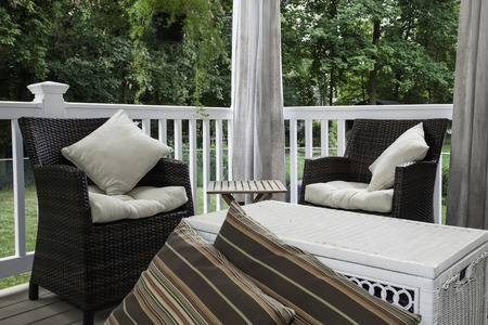 Two resin wicker chairs sit on a covered deck; they have cream colored cushions and pillows;  canvas curtains hang in the background; a white wicker chest serves as a coffee table; striped floor pillows are in the foreground Stock Photo