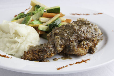 A white plate holds pine nut encrusted asiago chicken with a side of mashed potatoes and fresh mixed vegetables   Paprika is sprinkled around the edge of the plate  photo