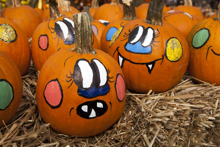 Small pumpkins are painted with funny faces for Halloween
