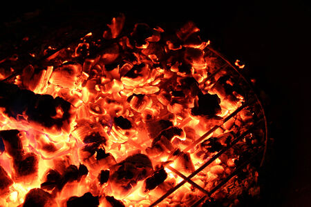 Red hot coals are all that remain of a campfire as it slowly burns out Stock Photo