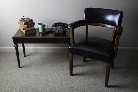 arredamento classico: Una foto degli interni stile retrò è mostrato con una sedia metà del secolo moderno, libri antichi, tazza di caffè, gli occhiali, e telefono nero rotante luce splende dal lato sinistro dell'immagine