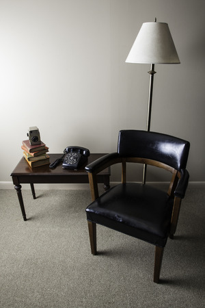 A retro style interior photo is shown with a mid-century modern chair, old books, classic camera, and black rotary telephone  Light is shining in from the left side of the image  photo