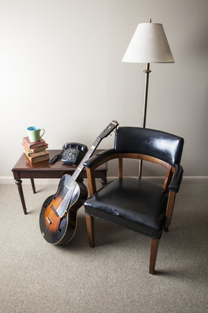 A retro style interior photo is shown with a mid-century modern chair, old books, coffee mug, accoustic guitar, and black rotary telephone  Light is shining in from the left side of the image  photo