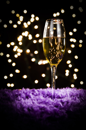 champagne glass: A champagne glass sits atop a purple fur surface; white bokeh in background; perfect for Christmas and New Years; red lipstick marks stain the rim of the glass Stock Photo