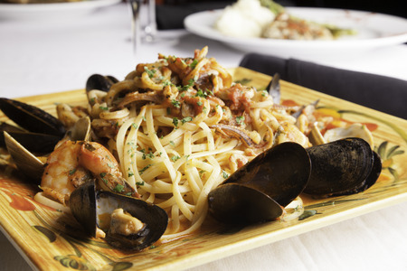 decadent: A colorful platter holds seafood fra diavolo over linguine   Fresh littleneck clams, mussels, shrimp, and squid are piled over the linguini with fresh basil sprinkled on top