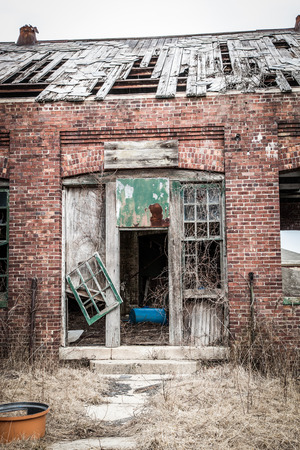 falling apart: An old building is in ruins; the roof is falling apart; garbage all over the place; vertical format