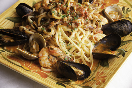 A colorful platter holds seafood fra diavolo over linguine   Fresh littleneck clams, mussels, shrimp, and squid are piled over the linguini with fresh basil sprinkled on top