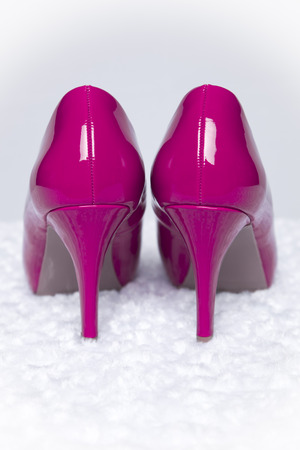 hot pink: A pair of hot pink pumps sit atop a white fur surface with a white background