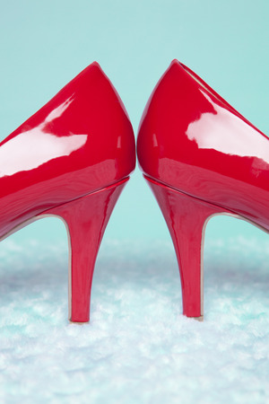 A pair of sexy, red patent leather pumps sit atop a white and teal fur surface with a teal background; vintage colortones photo