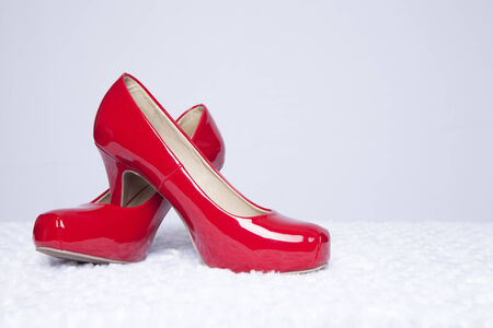 A pair of sexy, red patent leather pumps sit atop a white fur surface with a white background photo