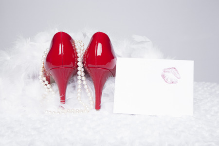 A pair of sexy, red patent leather pumps sit atop a white fur surface with a white background; pearls and a white boa surround the shoes; a love note with a lipstick kiss sit to the side photo