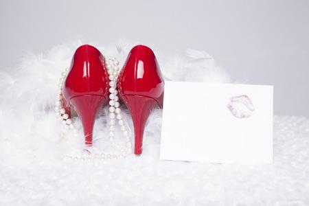 white fur: Un par de bombas de charol rojo sexy se sientan encima de una superficie de piel blanca con un fondo blanco; perlas y una boa blanca rodean los zapatos; una nota de amor con un beso del l�piz labial sentarse al lado
