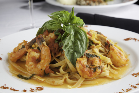 A white plate holds linguine with shrimp in a fra diavolo sauce, topped with fresh basil. Paprika is sprinkled on the sides of the plate for decoration. Everything sits on a white tablecloth. photo