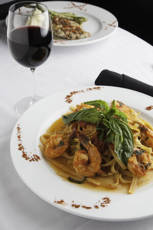 A white plate holds linguine with shrimp in a fra diavolo sauce, topped with fresh basil. Paprika is sprinkled on the sides of the plate for decoration.  A glass of red wine and a black napkin roll of utensils surrounds the plate.  Another dish can be see photo