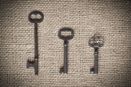 Three old metal skeleton keys sitting on a piece of brown burlap; horizonal format and vignetted edges for a vintage effect photo