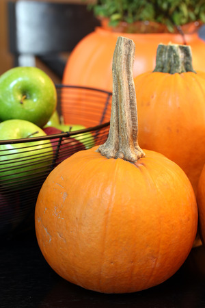 A small vibrant pumpkin is in the foreground of a still life of autumn favorites   In the background is a black fruit basket full of apples