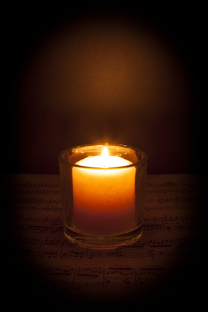 A candle glows in the darkness on top of sheet music; dark vignette Stock fotó