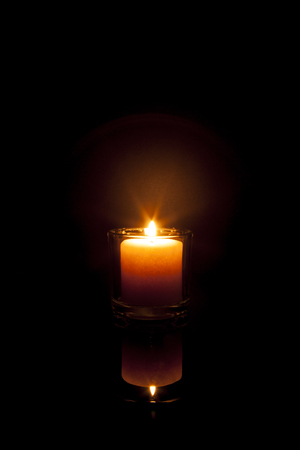 burned out: A candle glows in the darkness and reflects off a black surface; warm orange colortones